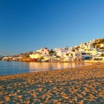 Mykonos Beach at sunset with the white washed building in background