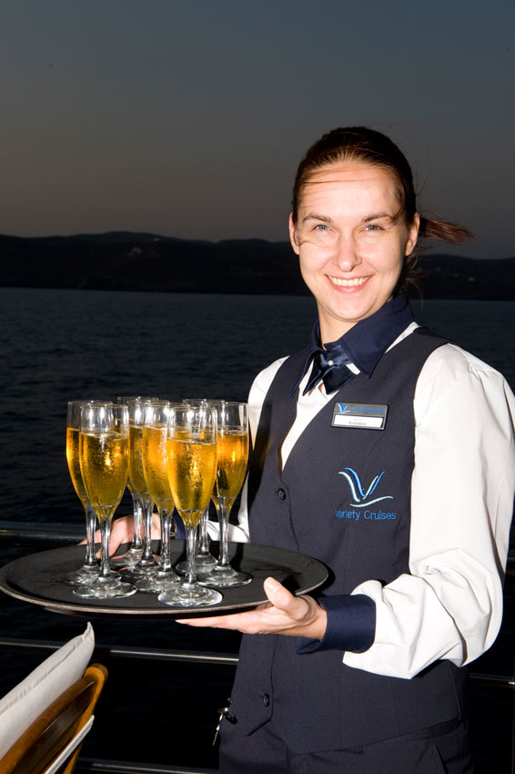 Waitress serving drinks with a smile on a Variety cruise