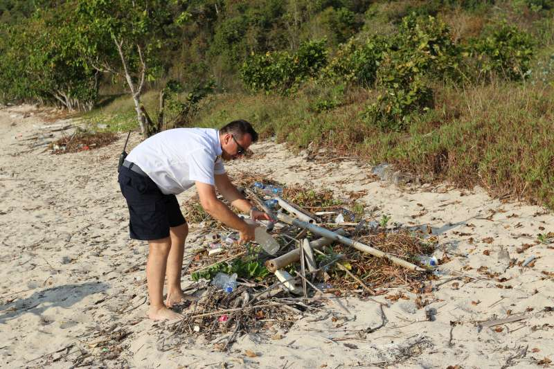 Captain Leontios examining detritus on the beach at Flores Island, Indonesia